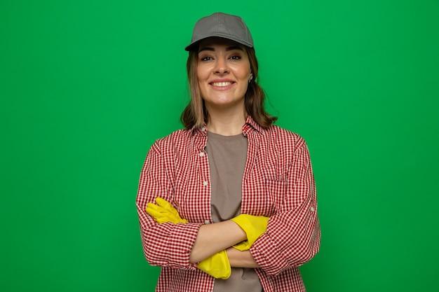 격자 무늬 셔츠와 고무 장갑을 끼고 모자를 쓴 젊은 청소 여성이 녹색 배경 위에 팔짱을 낀 채 즐겁게 웃고 있는 카메라를 바라보고 있습니다.