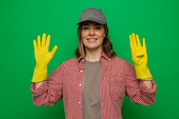 緑の背景の上に立っている指で9番を示しているカメラの笑顔を見てゴム手袋を着用している格子縞のシャツとキャップの若いクリーニング女性
