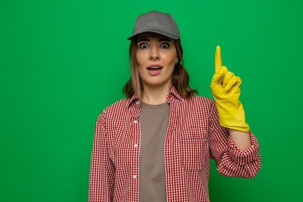 체크 무늬 셔츠와 고무 장갑을 낀 모자를 쓴 젊은 청소 여성이 카메라를 쳐다보며 녹색 배경 위에 새로운 아이디어가 있는 집게 손가락을 보여주는 것에 놀랐습니다.