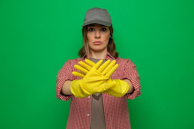 緑の背景の上に立っている手で停止ジェスチャーを作る深刻な顔でカメラを見てゴム手袋を着用した格子縞のシャツとキャップの若いクリーニング女性