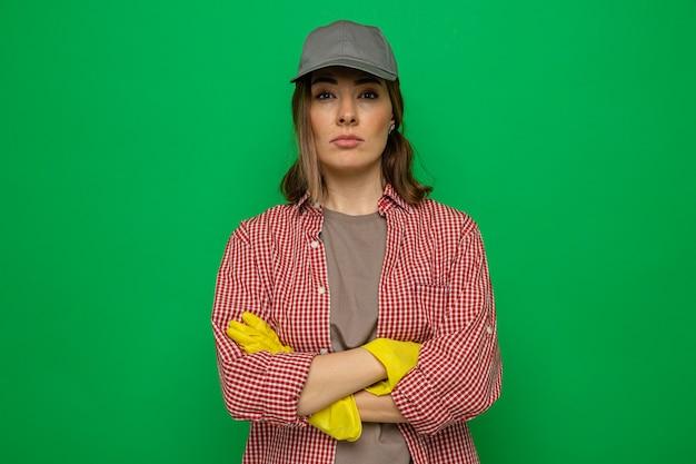 緑の背景の上に立って腕を組んで真面目な顔でカメラを見てゴム手袋を着用した格子縞のシャツとキャップの若い掃除の女性