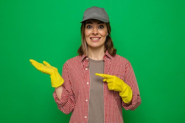 緑の背景の上に立っている彼女の腕に人差し指で指している彼女の手の腕を提示して笑顔でカメラを見てゴム手袋を着用した格子縞のシャツとキャップの若いクリーニング女性