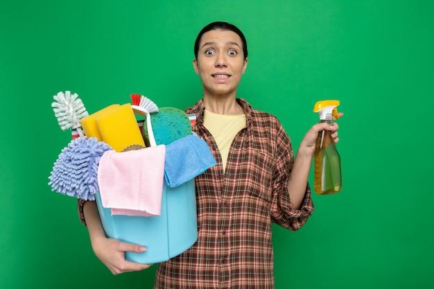 청소 도구와 청소 스프레이가 있는 양동이를 들고 있는 격자 무늬 셔츠를 입은 젊은 청소 여성은 녹색 위에 서서 놀라고 혼란스러워합니다.