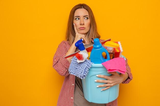 Молодая уборщица в клетчатой рубашке, держащая ведро с инструментами для уборки, озадаченно смотрит в сторону