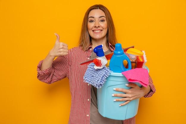 格子縞のシャツを着た若い掃除婦がバケツを持って掃除道具を持って元気に笑顔で親指を立て