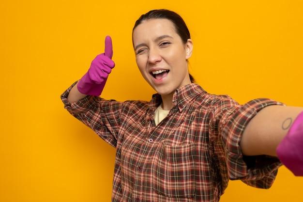 고무장갑을 낀 체크무늬 셔츠를 입은 젊은 청소 여성은 주황색 벽 위에 엄지손가락을 치켜들며 즐겁게 웃고 있는 앞을 바라보며 행복하고 긍정적인 미소를 짓고 있다
