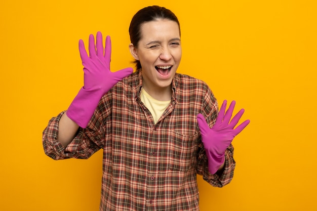 고무장갑을 낀 체크무늬 셔츠를 입은 젊은 청소부 여성은 주황색 벽 위에 손바닥이 서 있는 모습을 보고 웃고 윙크한다.