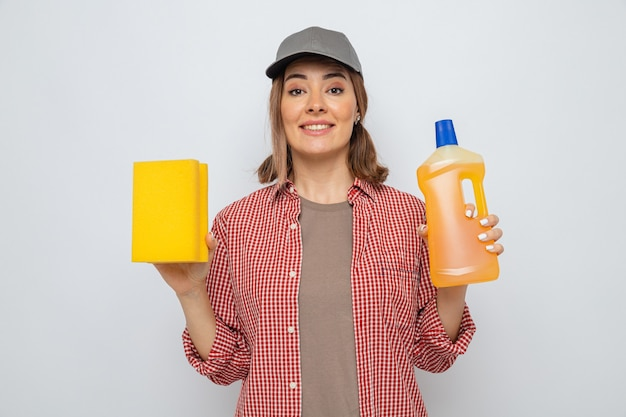 Young cleaning woman in plaid shirt and cap holding bottle of cleaning supplies and sponge looking at camera smiling cheerfully happy and positive standing over white background