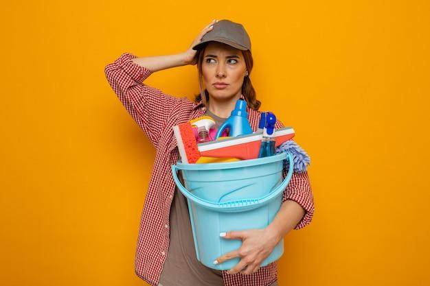 Giovane donna delle pulizie in camicia a quadri e berretto che tiene il secchio con strumenti per la pulizia che guarda da parte confuso con la mano sulla testa in piedi su sfondo arancione