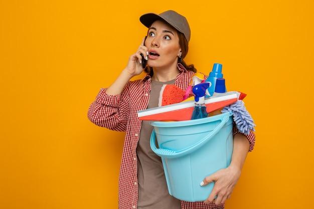 Giovane donna delle pulizie in camicia a quadri e cappello che tiene il secchio con strumenti per la pulizia che sembra sorpresa mentre parla al telefono cellulare in piedi su sfondo arancione orange