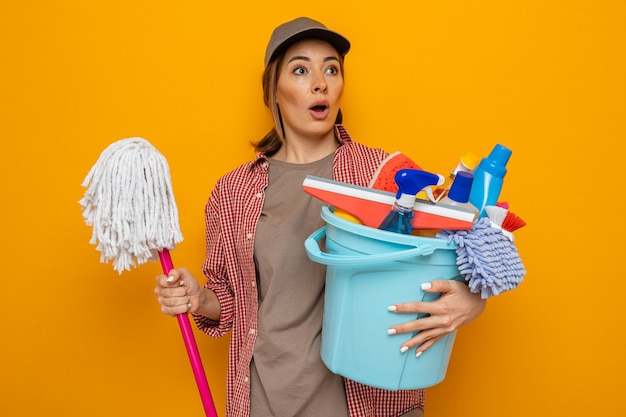 Young cleaning woman in plaid shirt and cap holding bucket with cleaning tools and mop looking aside amazed and surprised