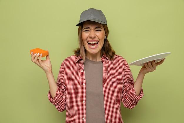 Giovane donna delle pulizie in camicia a quadri e cappello che tiene piatto e spugna guardando la telecamera felice ed eccitata in piedi su sfondo verde