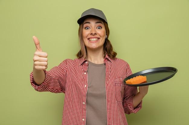 Giovane donna delle pulizie in camicia a quadri e cappello che tiene piatto e spugna che sembrano sorridenti e mostrano i pollici in su