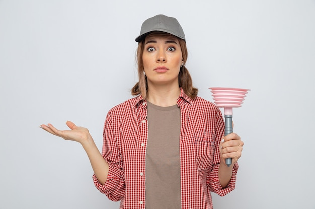 Young cleaning woman in plaid shirt and cap holding plunger looking at camera surprised and confused standing over white background