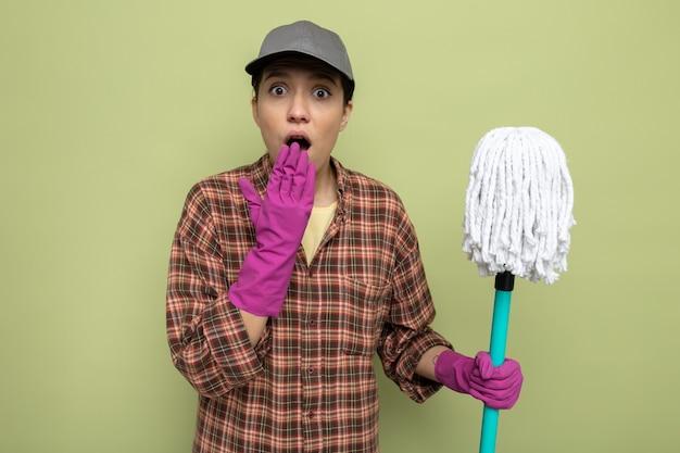 Giovane donna delle pulizie in camicia a quadri e berretto in guanti di gomma che tiene mop guardando davanti stupito e scioccato che copre la bocca con la mano in piedi sul muro verde