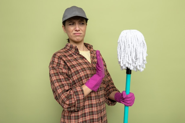 Young cleaning woman in plaid shirt and cap in rubber gloves holding mop looking at it with disgusted expression making defense gesture standing on green