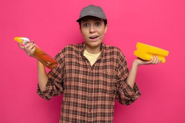 Giovane donna delle pulizie in camicia a quadri e berretto in guanti di gomma che tengono spugna e spray per la pulizia confuso allargando le braccia ai lati in piedi sul rosa