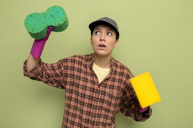Young cleaning woman in plaid shirt and cap in rubber gloves holding sponges looking up confused standing over green wall