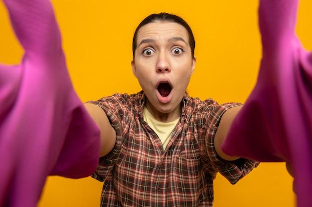 Giovane donna delle pulizie in camicia a quadri e berretto in guanti di gomma che si fa selfie stupita e sorpresa in piedi sul rosa