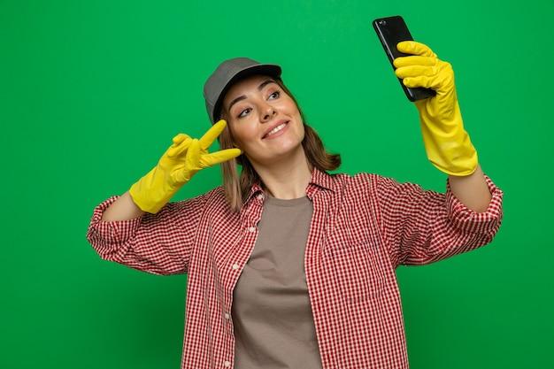 Giovane donna delle pulizie in camicia a quadri e berretto che indossa guanti di gomma facendo selfie utilizzando smartphone sorridendo allegramente mostrando v-sign