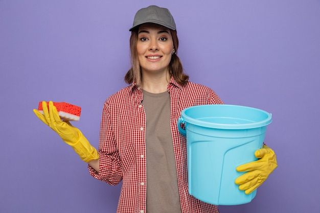 Young cleaning woman in plaid shirt and cap wearing rubber gloves holding bucket and sponge looking at camera smiling confident standing over purple background