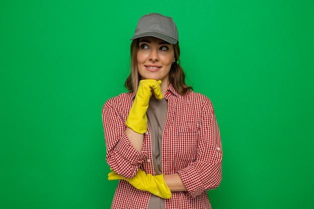 Giovane donna delle pulizie in camicia a quadri e berretto che indossa guanti di gomma che guarda da parte con un sorriso sul viso con espressione pensierosa
