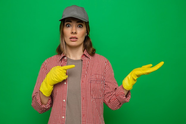 Young cleaning woman in plaid shirt and cap wearing rubber gloves looking at camera confused presenting with arm of her hand pointing with index finger at her arm standing over green background