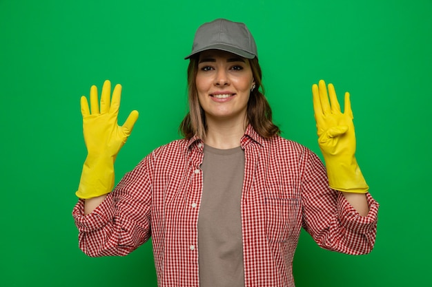 Young cleaning woman in plaid shirt and cap wearing rubber gloves looking at camera smiling showing number nine with fingers standing over green background