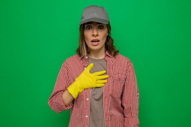 Giovane donna delle pulizie in camicia a quadri e berretto che indossa guanti di gomma guardando la telecamera sorpresa tenendo la mano sul petto in piedi su sfondo verde