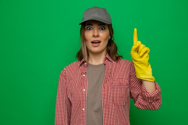 Young cleaning woman in plaid shirt and cap wearing rubber gloves looking at camera surprised showing index finger having new idea standing over green background