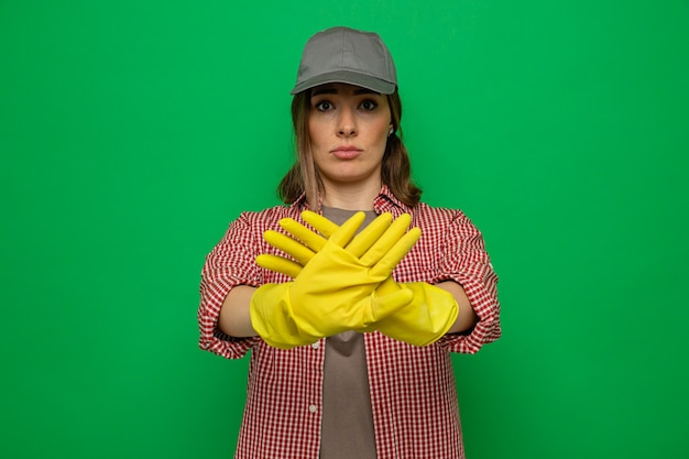 Giovane donna delle pulizie in camicia a quadri e berretto che indossa guanti di gomma che guarda la telecamera con una faccia seria che fa un gesto di arresto con le mani in piedi su sfondo verde