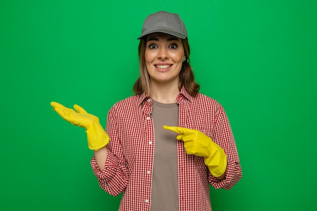 Young cleaning woman in plaid shirt and cap wearing rubber gloves looking at camera with smile presenting with arm of her hand pointing with index finger at her arm standing over green background