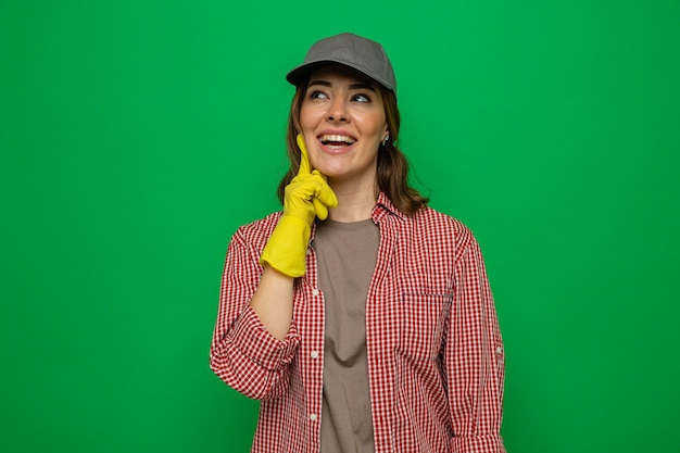 Giovane donna delle pulizie in camicia a quadri e berretto che indossa guanti di gomma guardando in alto sorridendo allegramente sognando in piedi su sfondo verde