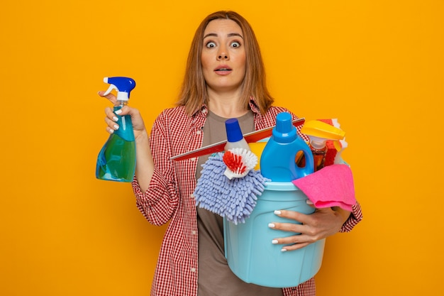 Young cleaning woman in plaid shirt holding bucket with cleaning tools and cleaning spray looking surprised