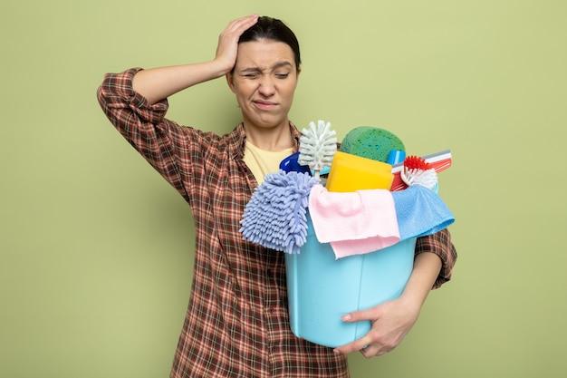Giovane donna delle pulizie in camicia a quadri che tiene in mano un secchio con strumenti per la pulizia che sembra confuso e dispiaciuto in piedi sul verde