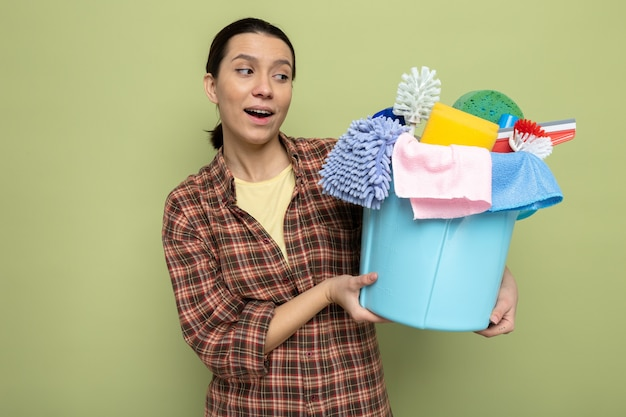 Young cleaning woman in plaid shirt holding bucket with cleaning tools looking at them with smile on face standing over green wall