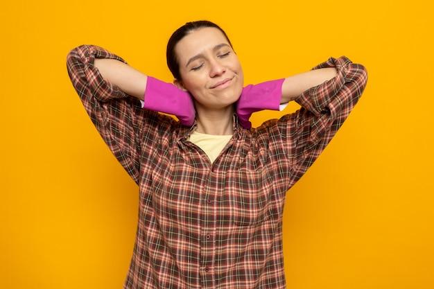 Giovane donna delle pulizie in camicia a quadri in guanti di gomma felice e contenta che si allunga in piedi sul muro arancione