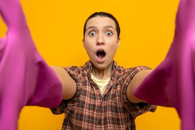 Giovane donna delle pulizie in camicia a quadri in guanti di gomma che guarda davanti stupita e sorpresa con gli occhi spalancati in piedi sul muro arancione