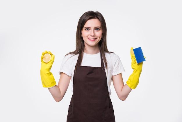 Молодая уборщица, стоящая и держащая губку против