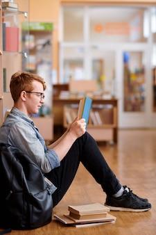 Молодой умный человек в повседневной одежде читает книгу, сидя на полу библиотеки после занятий