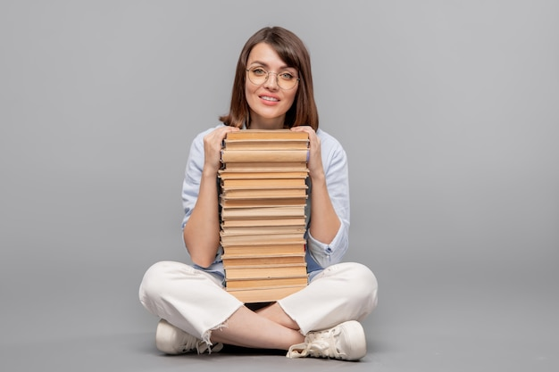 Молодой умный студент сидит на полу с высокой стопкой книг перед ней и смотрит на вас
