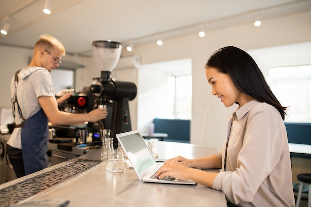 Young client of cafeteria sitting by table and surfing in the net while barista preparing fresh coffee on background