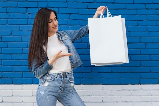 Giovane cliente che mostra la borsa bianca dello spazio della copia