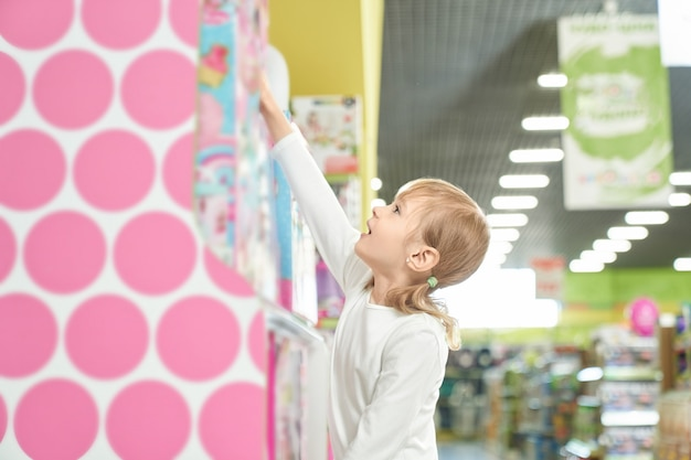 Young client of store taking from upper shelf box with toy.