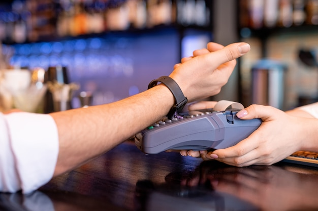 Молодой клиент с умными часами держит запястье над платежным автоматом, оплачивая заказ в современном ресторане или кафетерии
