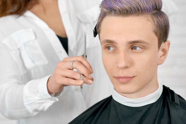 Молодой клиент с тонированными лиловыми волосами, сидя белый прическа.