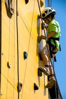 Молодой мальчик-альпинист карабкается по стене - ребенок веселится в одиночестве, пока он карабкается - наслаждаясь моментом - голубое небо на заднем плане