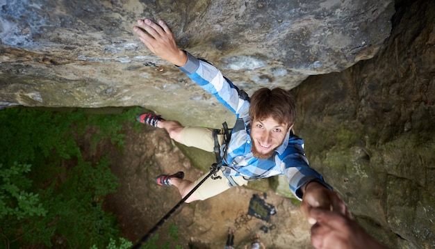 Young climber smiling, hanging on rope on rock. man falling down from the cliff holding friend's hand