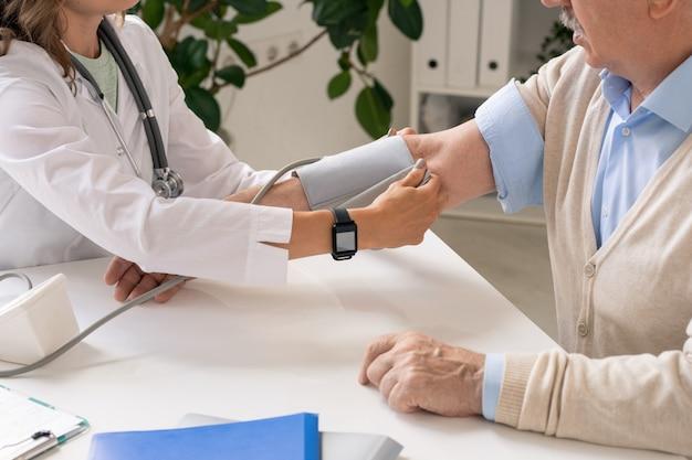 Молодой врач в белом халате надевает часть тонометра на руку пожилого пациента, собираясь измерить его кровяное давление