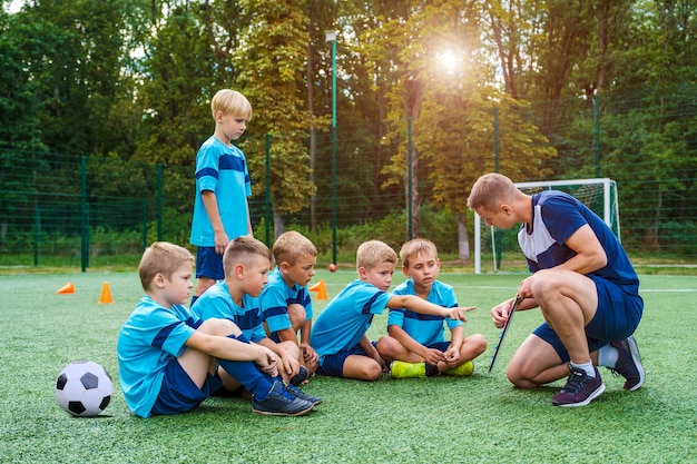 Young coach teaches little children the strategy of playing on football field